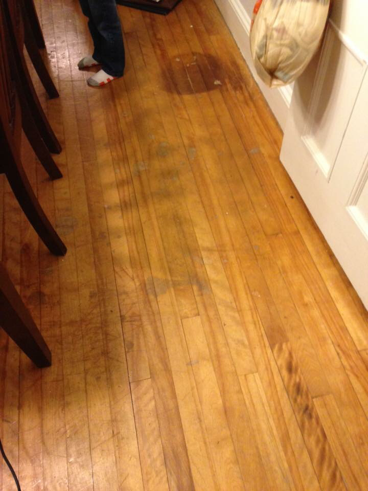 A picture of a water damaged hardwood floor ready to be refinished