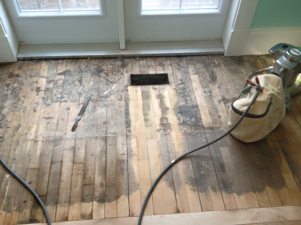 This hardwood floor with carpet glue. Remove the glue, sand and refinish the floor!